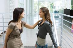 Mother and daughter standing face to face on stairs, both smiling at each other - stock photo