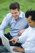 Two businessmen sitting side by side outdoors, both looking down at laptop Stock Photos
