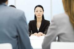 Executives in meeting, focus on businesswoman holding document in background Stock Photos