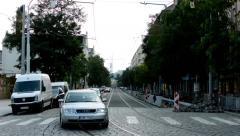 Urban street with passing cars and trams and buildings - people walking - road  Stock Footage