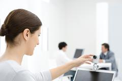 Businesswoman using webcam in office - stock photo