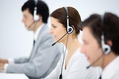 Call center, focus on woman wearing headset, smiling, side view - stock photo