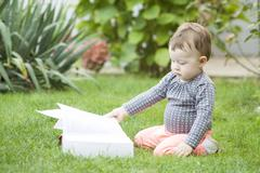 baby girl looking at a book in the park - stock photo