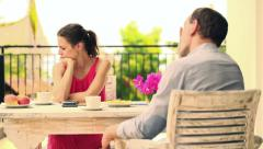 Bored, resentful couple sitting by the table on terrace HD Stock Footage