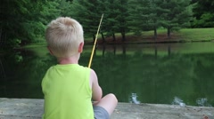 Small Boy Fishing On Dock Stock Footage