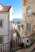 one of the narrow streets of alfama with the typical cobblestone staircases ( - stock photo