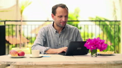 Man working on laptop by the table on terrace HD Stock Footage