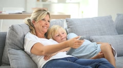 Mother and son in sofa watching tv Stock Footage