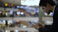 Stock Video Footage of Locked-On shot of a businessman using a mobile phone in shopping mall