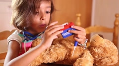 Girl playing doctor with teddy bear Stock Footage
