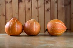Stock Photo of three pumpkins abreast on  table
