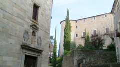 Pan on back of Cathedral of Girona from narrow street with cypress Stock Footage