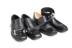 two pairs black man's shoe and a belt - stock photo