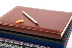 felt-tip pen on a pile of writing-books and organizers - stock photo