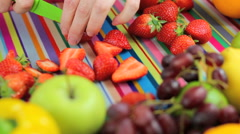 slicing strawberries in colorful kitchen scene - stock footage