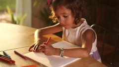 Beautiful girl drawing a house in paper with crayons Stock Footage