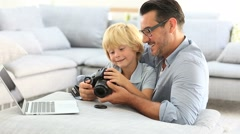 Man with little boy playing with reflex camera Stock Footage