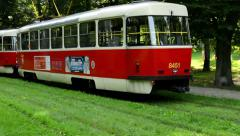 Passing tram in the park (trees) Stock Footage