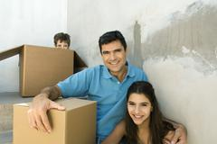 Family sitting on stairwell with cardboard boxes, boy hiding Stock Photos