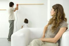 Man using drill to attach wood to wall, woman in foreground watching over her - stock photo