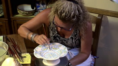 Woman artist in the workshop paints a bowl Stock Footage