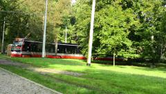 Passing tram in the park (trees) - sunny Stock Footage