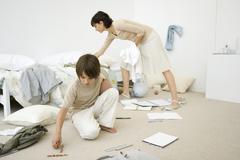 Mother helping boy clean messy room, full length Kuvituskuvat