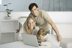 Family gathered around laptop computer, little boy typing, parents smiling at Stock Photos