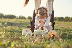 little baby seeing halloween pumpkin first time - stock photo
