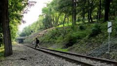 Man runs across the rails - the track for the train in the forest - trees Stock Footage