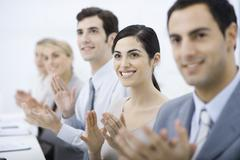Group of professionals clapping, smiling, focus on one woman Stock Photos