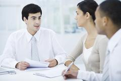Professionals sitting at table, discussing documents Stock Photos
