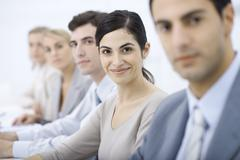 Professionals lined up, smiling at camera, selective focus Stock Photos