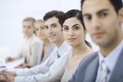 Professionals lined up, smiling at camera, selective focus - stock photo