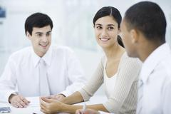 Young professionals sitting at table, focus on woman in center Stock Photos