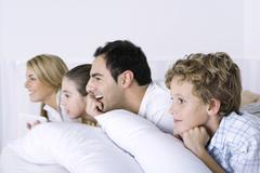 Family lying on bed, watching television, side view Kuvituskuvat