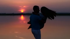 Silhouette man and woman dancing at sunset. Slow motion. Stock Footage