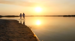 young happy couple running to the sea at sunset beach. Slow motion. - stock footage