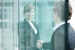 Businesswoman and businessman meet and shake hands at building entrance Stock Photos