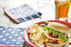 Cheeseburger loaded with toppings at patriotic cookout - stock photo
