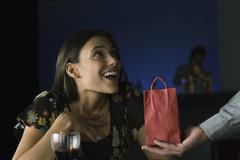 Woman being presented with gift, looking up in astonishment at giver Stock Photos
