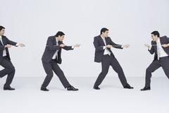 Businessman playing tug-of-war with clones of self, digital composite Stock Photos