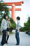 Group of friends chatting, traditional Japanese Torii gate in background - stock photo