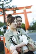 Young couple leaning against railing together, traditional Japanese Torii gate - stock photo