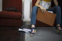 Woman holding file, sitting with legs apart, cropped Stock Photos