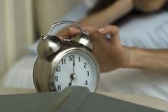 Woman's hand silencing alarm clock Stock Photos