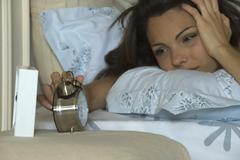 Young woman silencing alarm clock, holding head Stock Photos