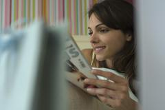 Young woman reading magazine, selective focus - stock photo