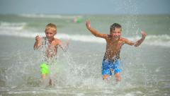 two happy  children splash and play in the sea. - stock footage