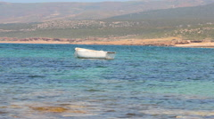 White rowing boat bobbing on an azure sea in Cyprus Stock Footage